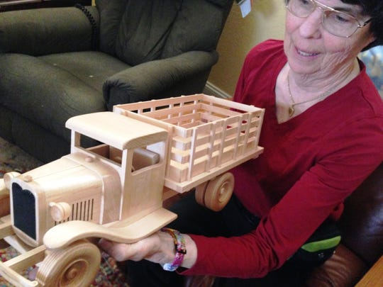 Deena Case-Pall, president of the Conejo Valley Woodworkers Association, holds a wooden toy truck made by her husband, Stephen, and Arlen Handberg, who are both members of the association.