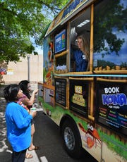 "Regina Perez, left, and her daughter, Celena Perez, talk with Carri Davoult after receiving their free Kona Ice treats Monday during the company's ""National Chill-Out Day"" for Tax Day."