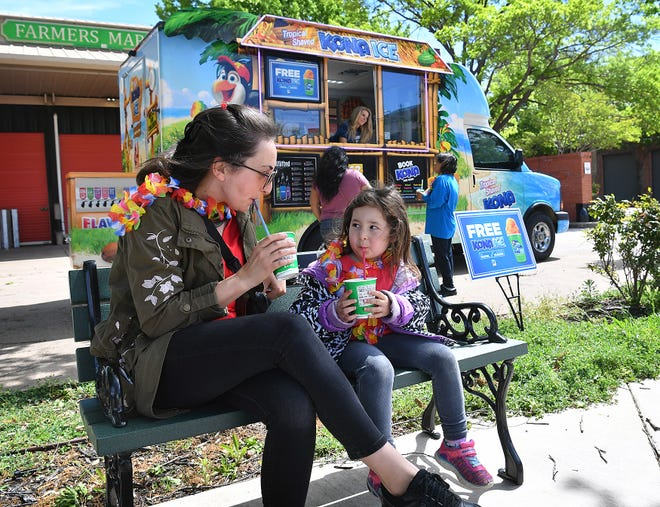 """Asya Yarali and her daughter, Handan Yarali, 4, enjoy a free Kona Ice at the Farmers Market Monday morning as part of Kona's """"National Chill-Out Day"""" which coincides with Tax Day each year."""