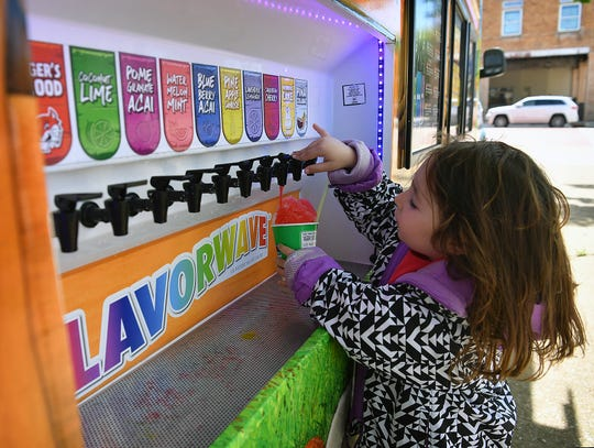 Handan Yarali, 4, adds cherry syrup to her Kona Ice Monday at the Farmers Market. Kona Ice gave out free snow cones for Tax Day from 11 a.m. to 1 p.m.