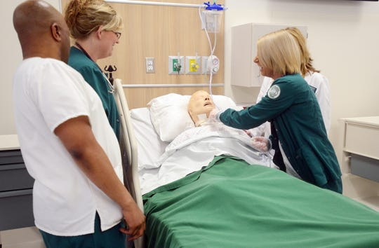 Patrick Mwanza, left, Brenda Spiker and Brooke Mellor demonstrate a trach suctioning in one of the new nursing labs at Ohio University-Zanesville.