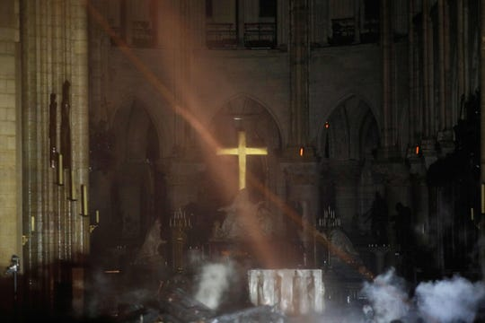 Smoke rises in front of the altar cross at Notre Dame Cathedral in Paris on April 15, 2019, after a fire engulfed the building.