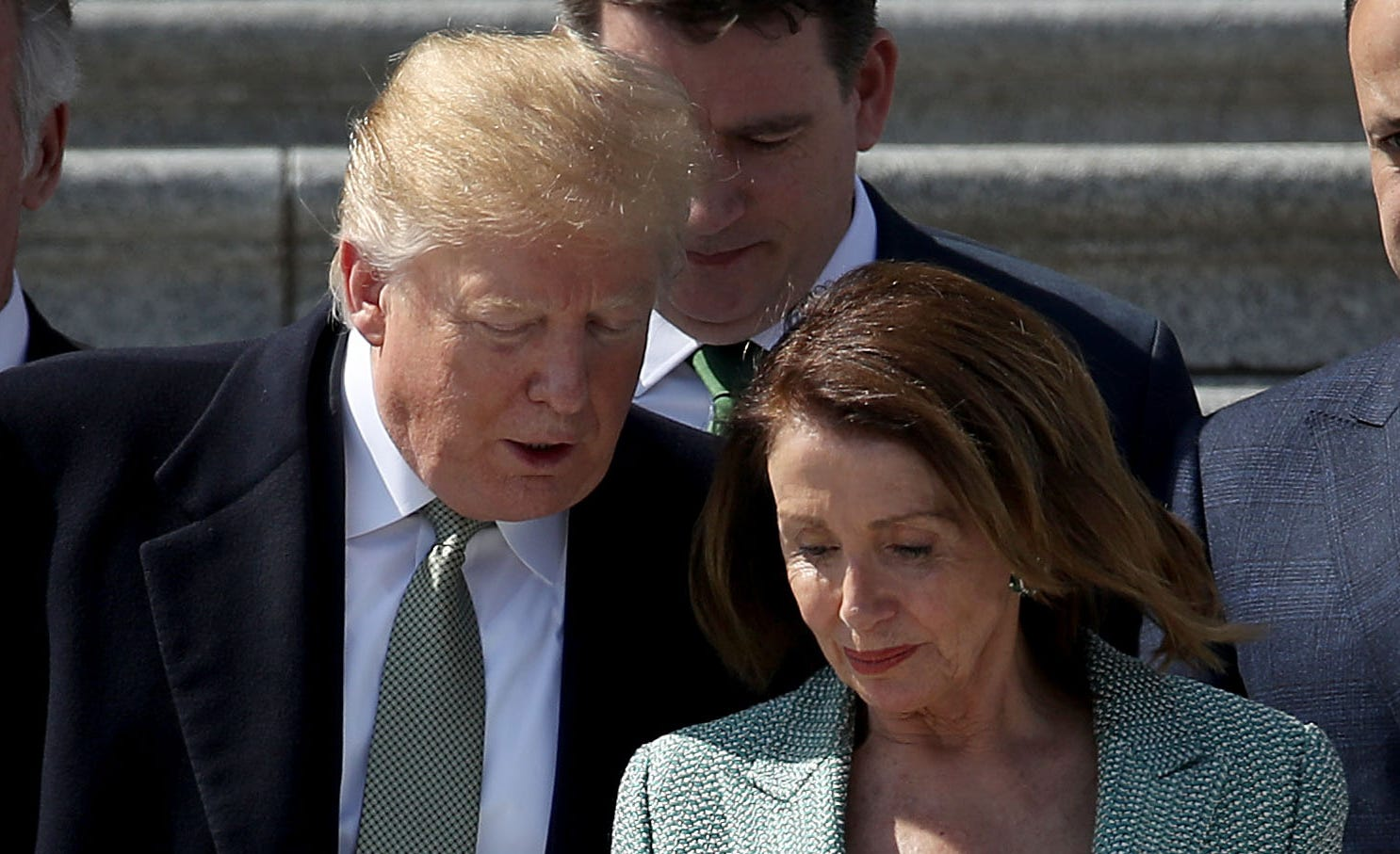 President Donald Trump confers with House Speaker Nancy Pelosi, D-Calif., while departing a St. Patrick's Day celebration at the Capitol in Washington, March 14, 2019.