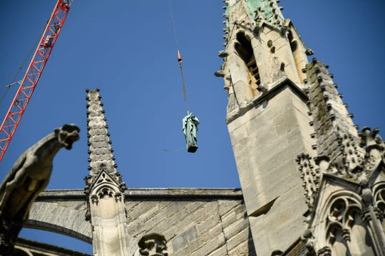 A crane lifts one of 16 copper statues off Notre-Dame-de-Paris Cathedral to be taken for restoration on April 11, 2019, before a devastating fire on April 15, 2019. The statues of the 12 apostles and the 4 evangelists sit around the spire of the cathedral.