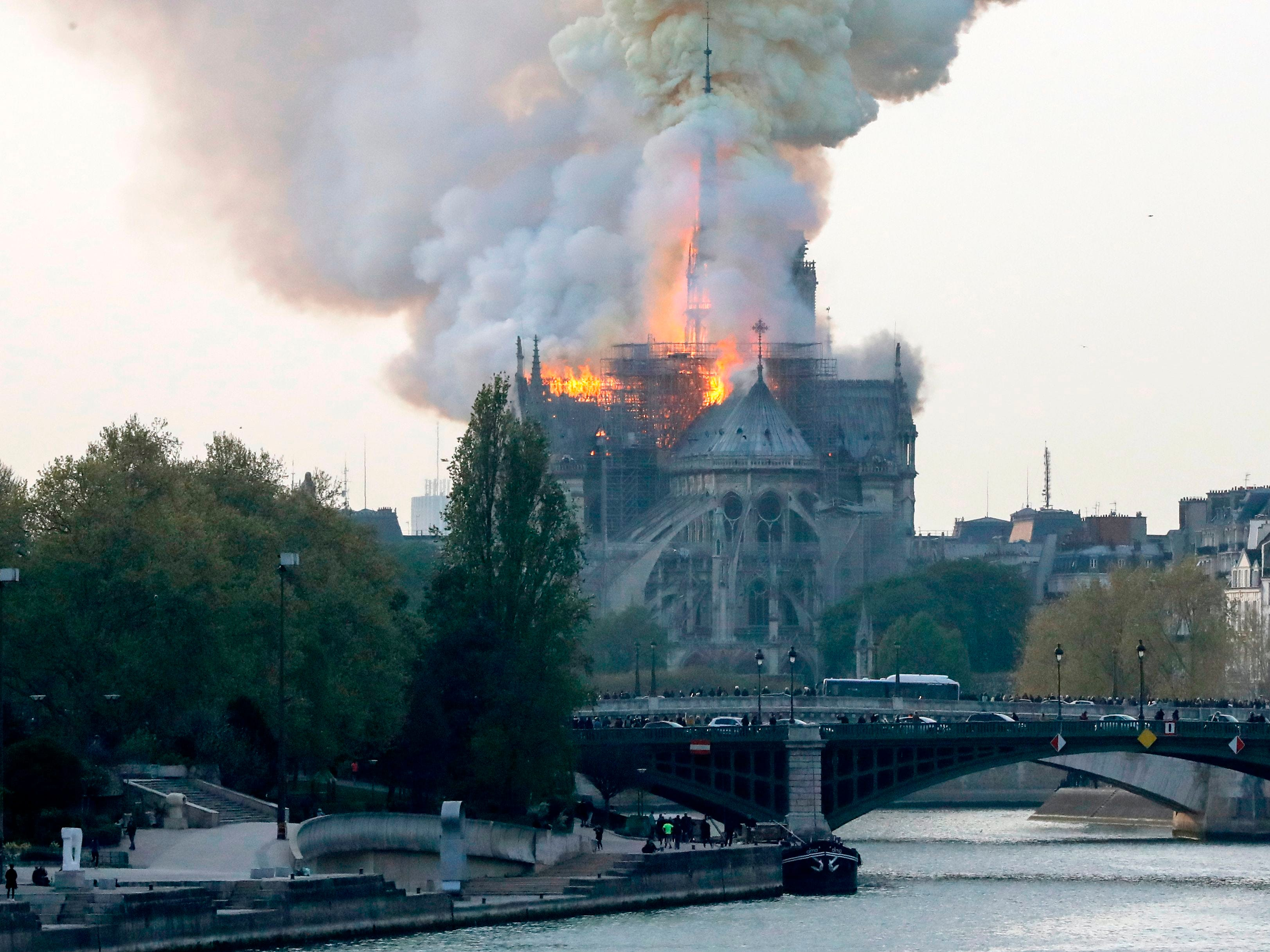 Smoke and flames rise during a fire at the landmark Notre Dame Cathedral.