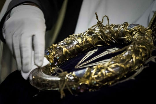 A priest wipes the Crown of Thorns at Notre Dame Cathedral in Paris, in April 2017.  The relic, venerated by Catholics as once worn by Jesus Christ, was threatened by a devastating fire at the cathedral on April 15, 2019.