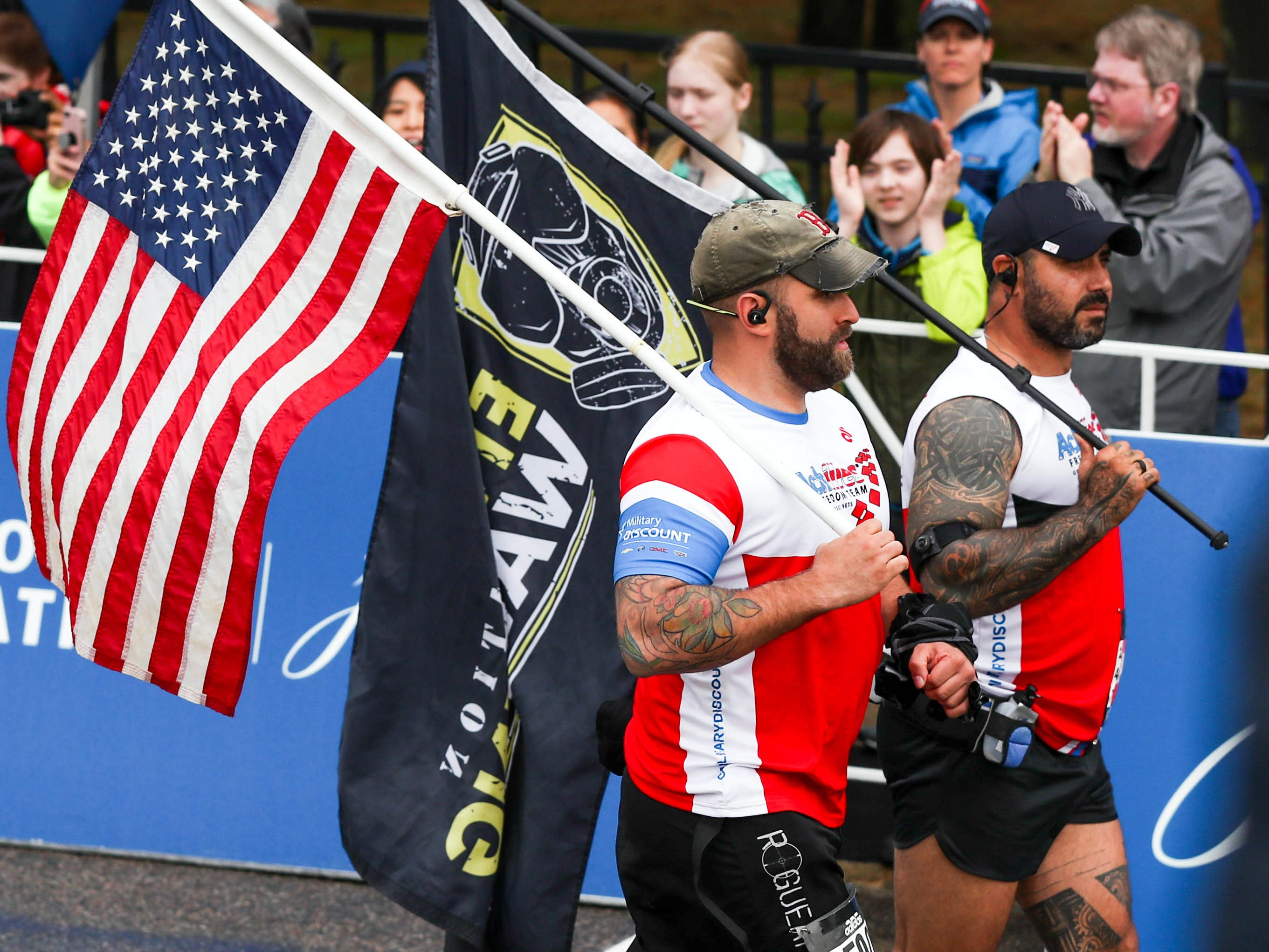 Christopher Reischel holds an American flag at the Boston Marathon starting line.