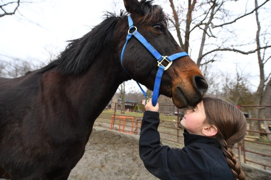 "Lacey Trezza, 8, works with ""Toby"" at JL Performance Horses in Poughquag, New York. Trezza is working on the farm throughout the year to help pay for her spot in its summer camp."