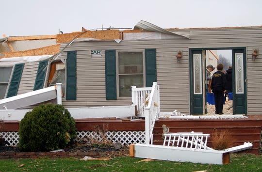 People search for personal items after severe weather damaged a home on Plymouth Springmill Road just south of the intersection of Ohio Route 96 in Shelby, Ohio, on April 14, 2019.