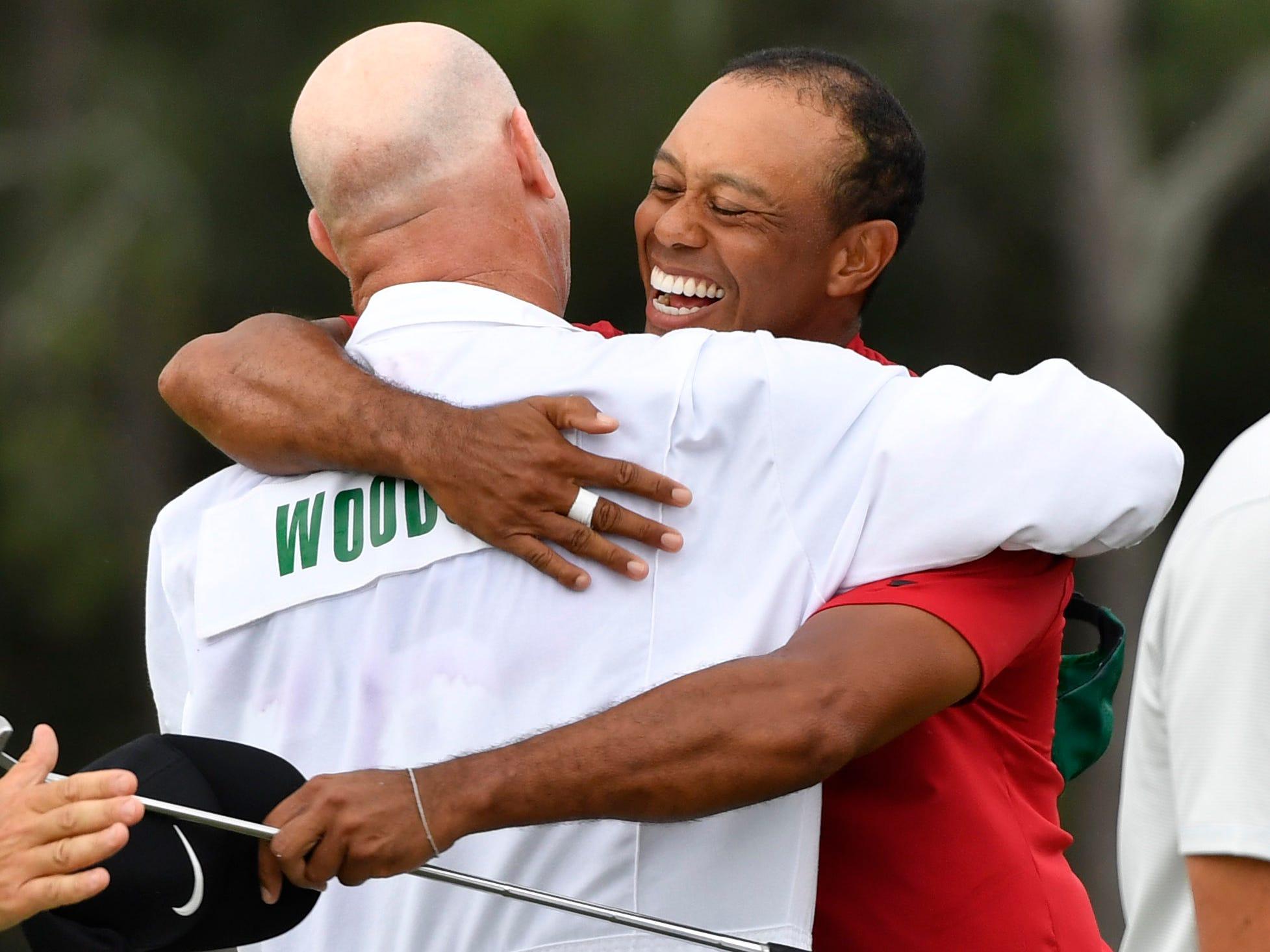 Tiger Woods hugs caddie Joe Lacava.