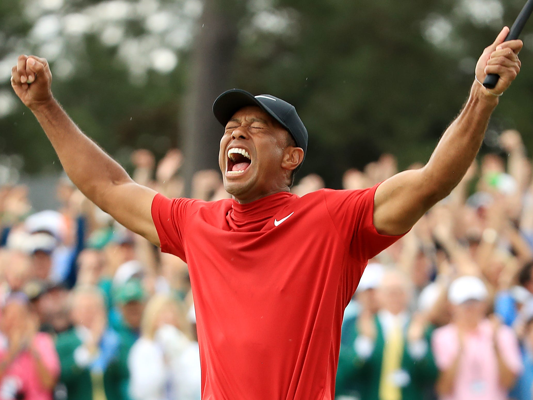 Tiger Woods of the United States celebrates after sinking his putt on the 18th green.