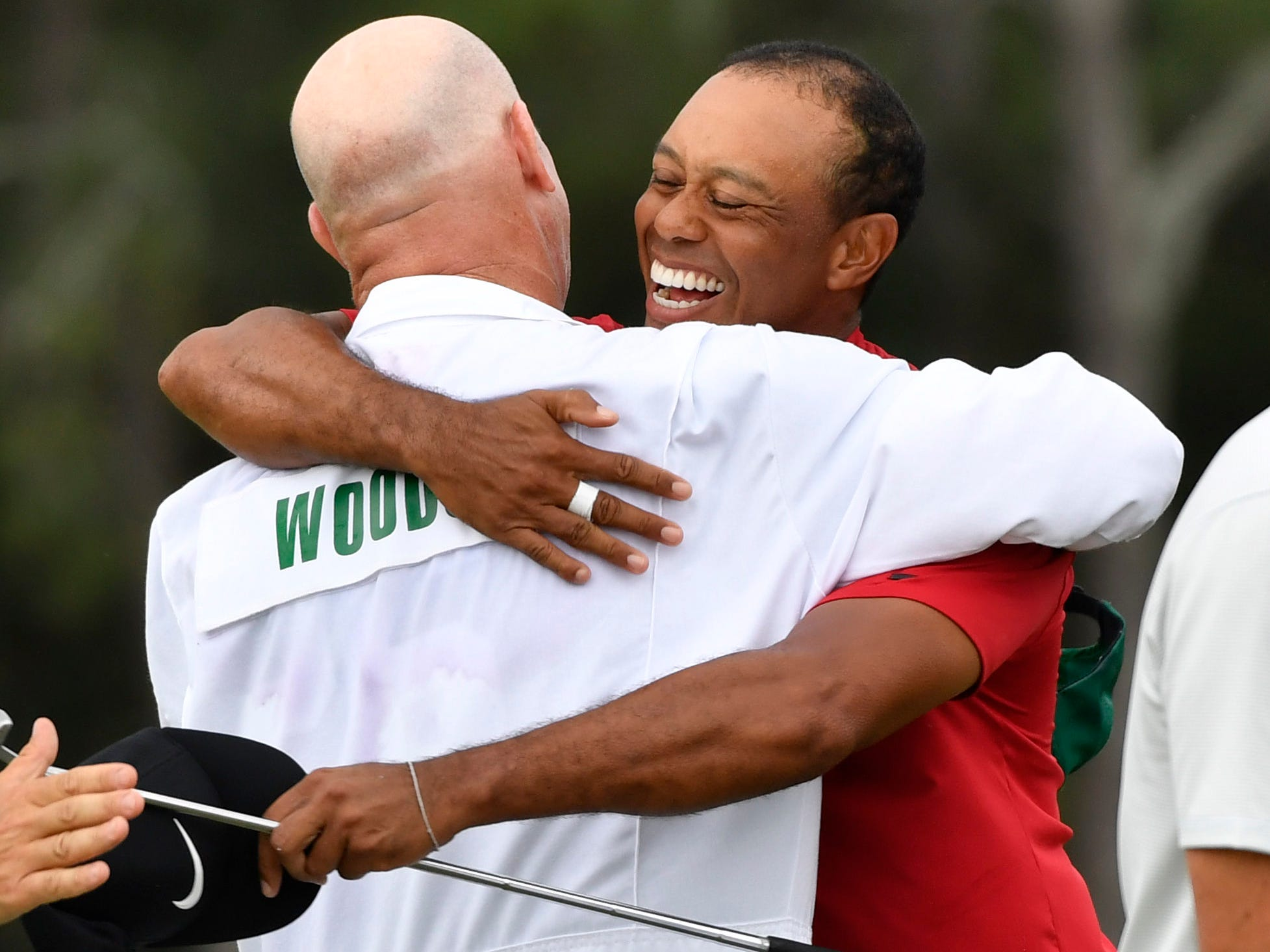 Apr 14, 2019; Augusta, GA, USA; Tiger Woods hugs caddie Joe Lacava after winning The Masters golf tournament at Augusta National Golf Club. Mandatory Credit: Michael Madrid-USA TODAY Sports ORG XMIT: USATSI-389786 ORIG FILE ID:  20190414_jla_mm1_225.jpg