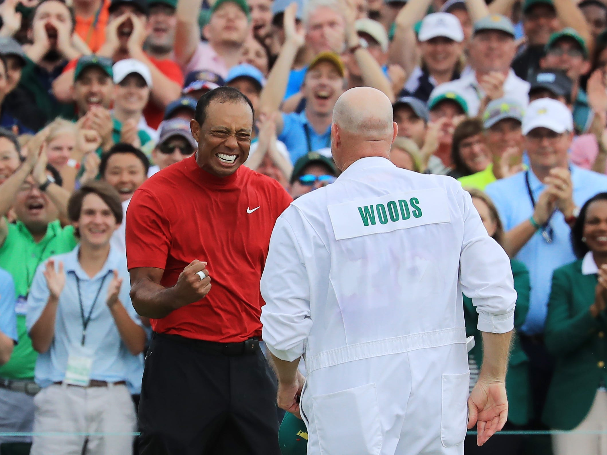 Tiger Woods celebrates with caddie Joe LaCava on the 18th green.