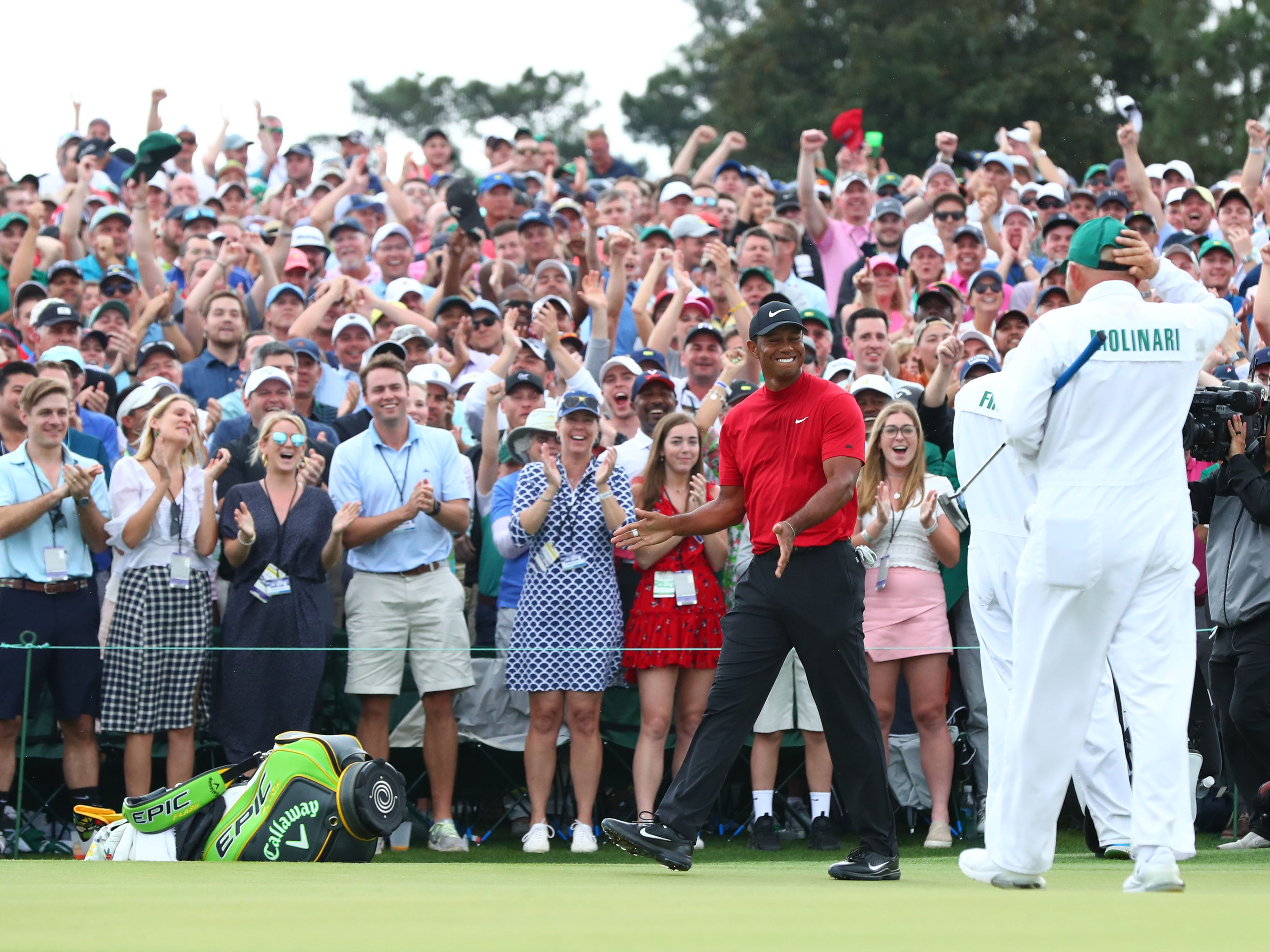 Fans cheer as Tiger Woods leaves the 18th green.