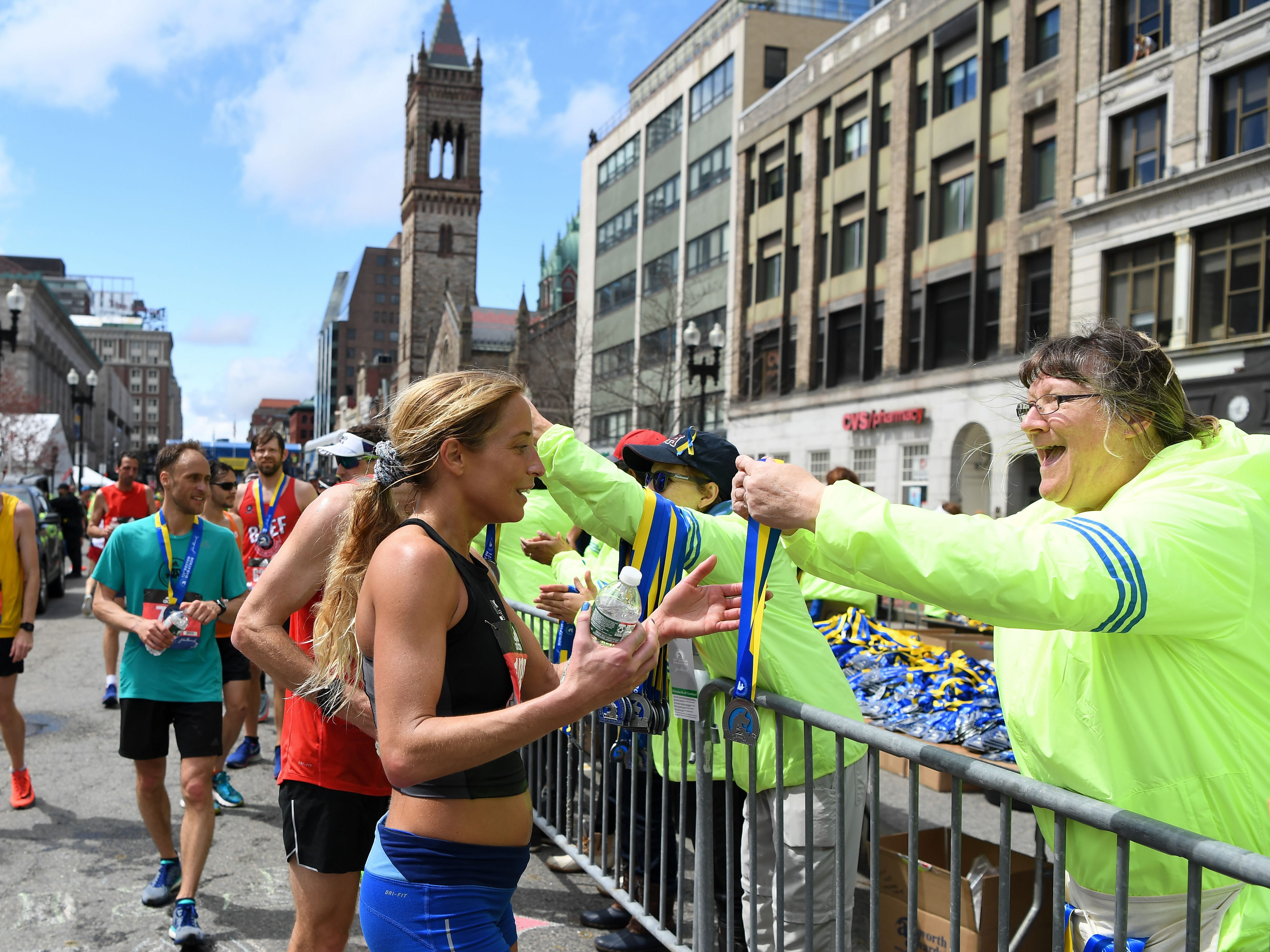 Volunteers hand out finisher medals at the 2019 Boston Marathon.
