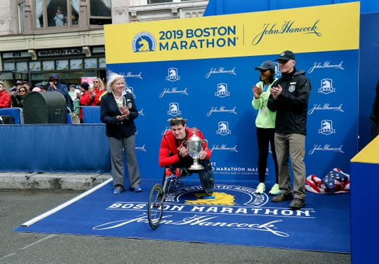 Daniel Romanchuk, of Urbana, Ill., holds the trophy after winning the men's handcycle division of the 123rd Boston Marathon on Monday, April 15, 2019, in Boston.
