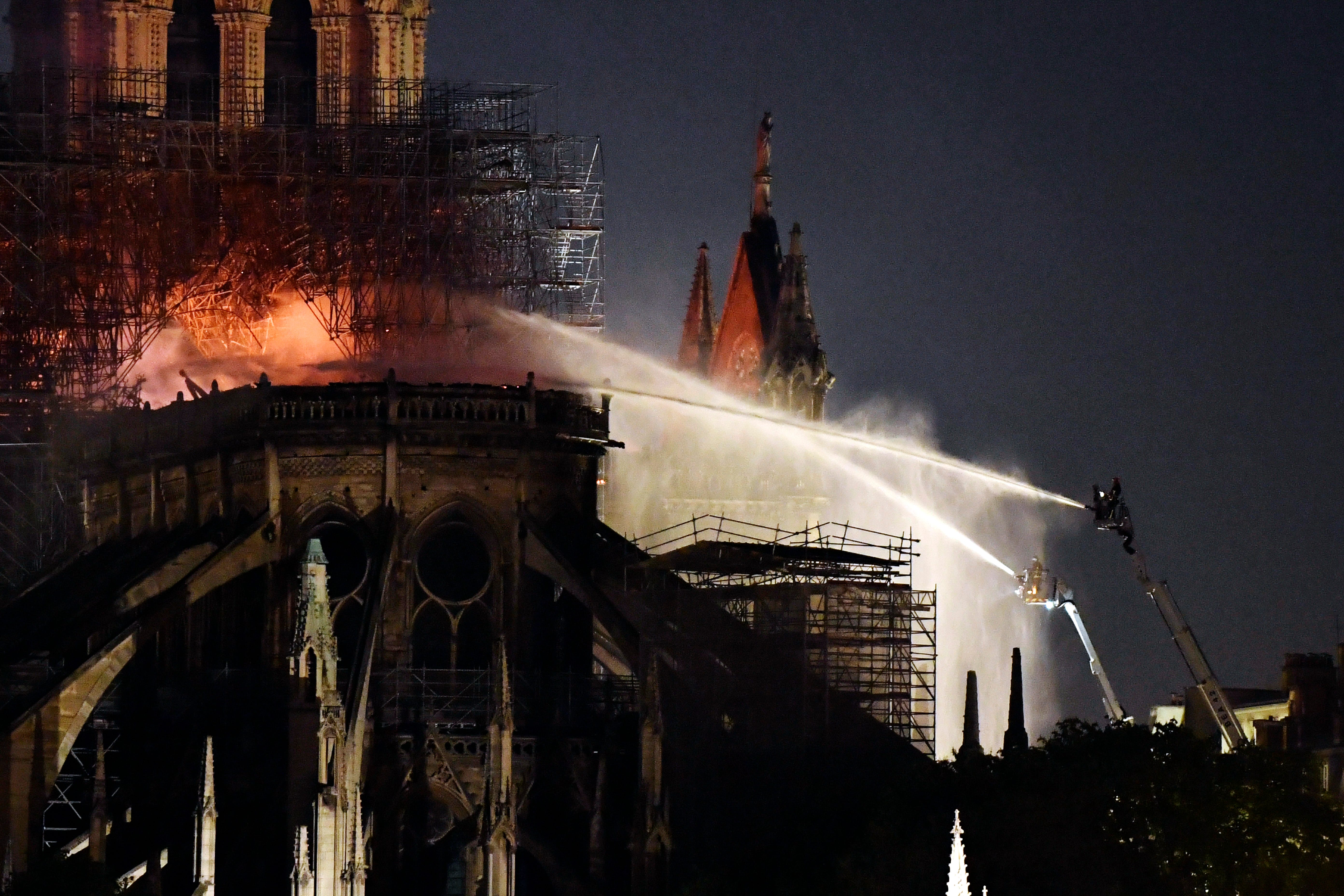 French firefighters spray water to put out a fire on the roof of the Notre Dame Cathedral in Paris on April 15, 2019.