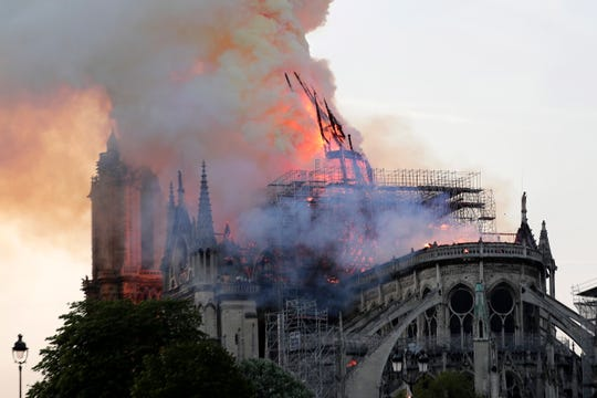 The spire collapses while flames are burning the roof of the Notre-Dame Cathedral.