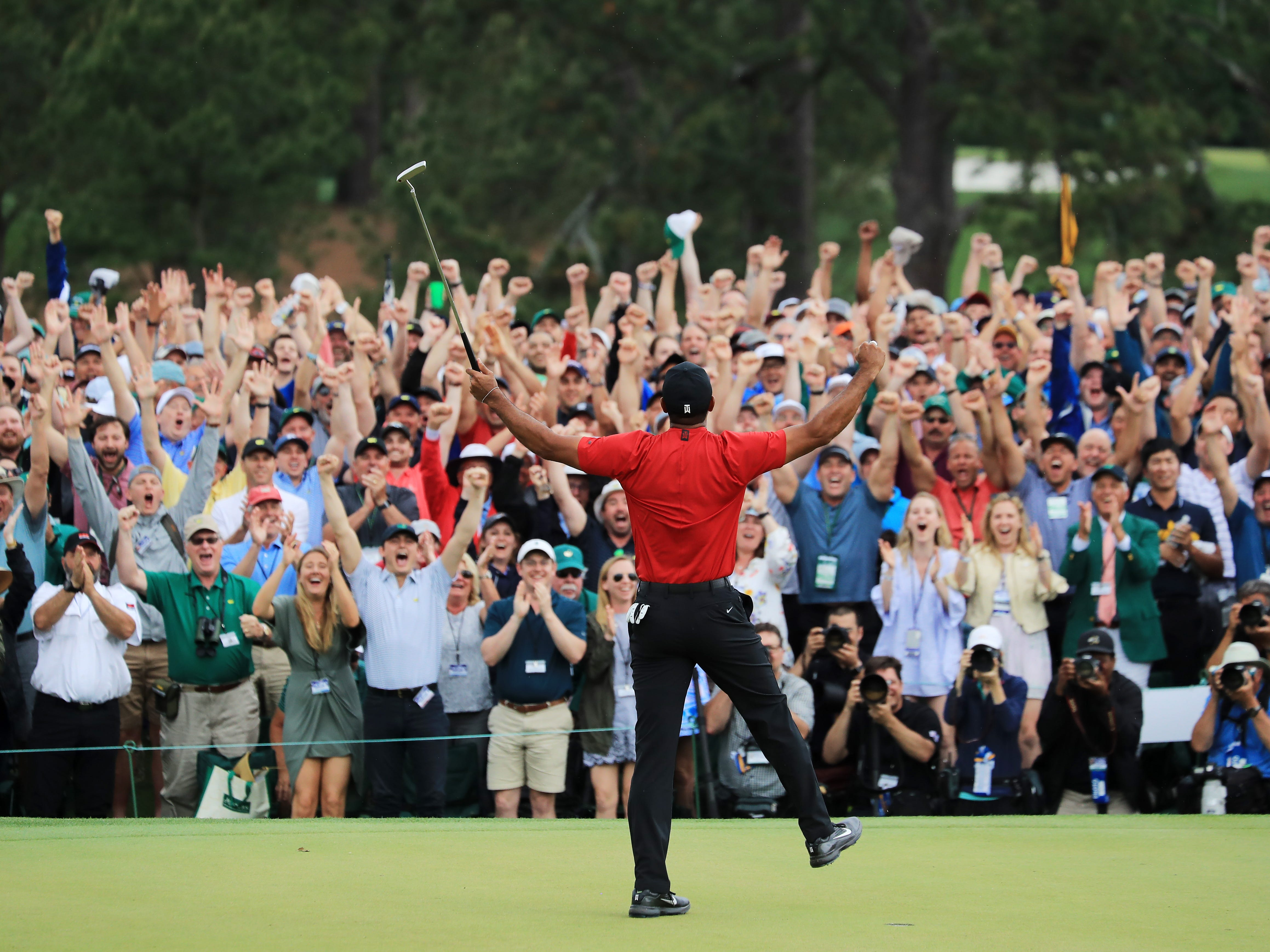 Patrons cheer as Tiger Woods of the United States celebrates after sinking his putt on the 18th green.