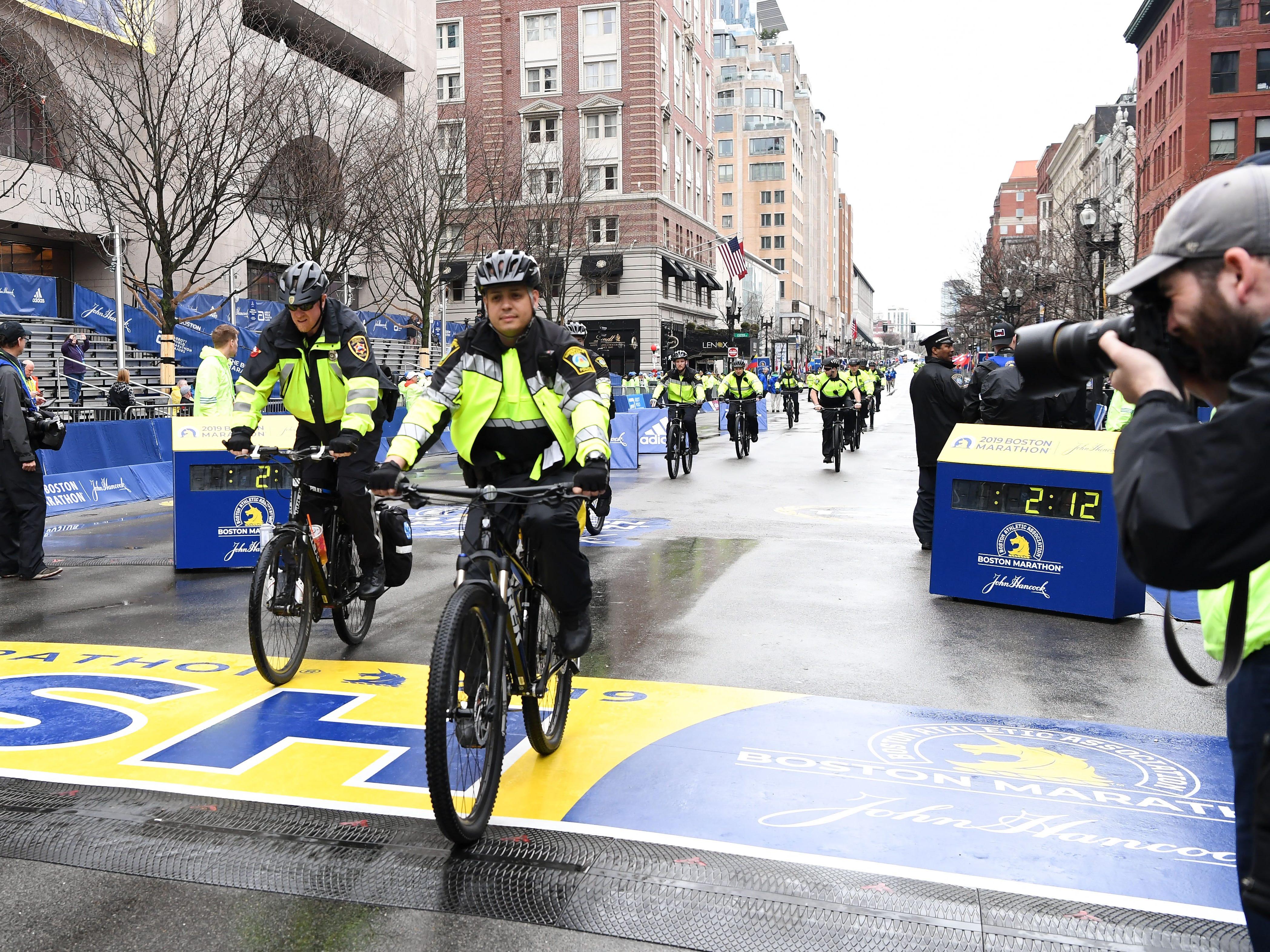 Boston police cross the finish line ahead of the 2019 Boston Marathon.