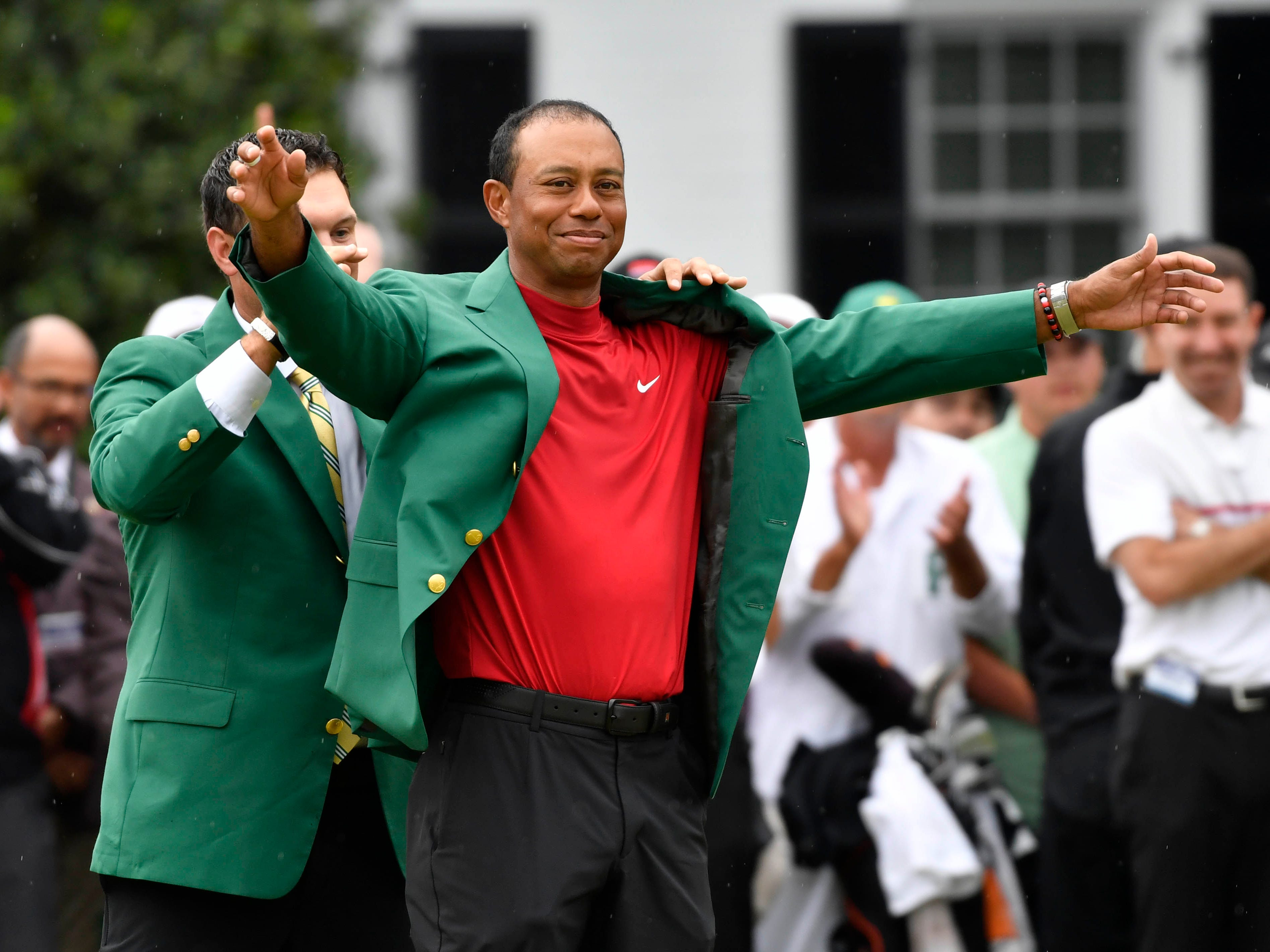 2018 winner Patrick Reed places the green jacket on 2019 winner Tiger Woods after the final round of The Masters golf tournament at Augusta National Golf Club.