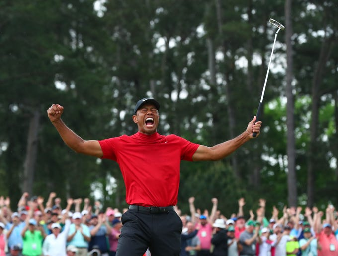 Tiger Woods celebrates after making a putt on the 18th green to win The Masters golf tournament at Augusta National Golf Club on April 14, 2019.