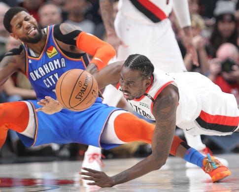 April 14: Trail Blazers forward Al-Farouq Aminu fights for a loose ball with Thunder forward Paul George during Game 1 in Portland.