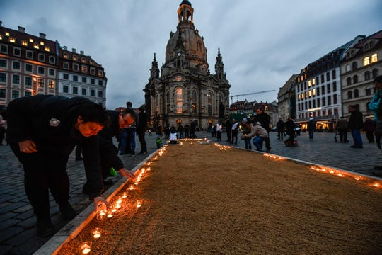 People place candles at the landmark 'Frauenkirche,' or Church of Our Lady, to commemorate the destruction of the city during World War II in Dresden, Germany, on Feb. 13, 2019.