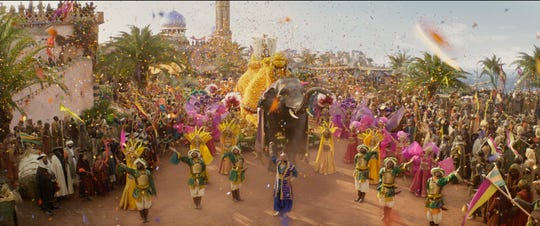 "The Genie (Will Smith, center) makes the kingdom of Agrabah a magical, musical place in Guy Ritchie's new live-action ""Aladdin."" (May 24)"