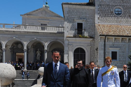 Prince Harry of Great Britain (R) visits Montecassino Abbey with father Antonio (C) on May 18, 2014 in Cassino for the 70th anniversary of a key World War II battle in which tens of thousands died. Army captain Harry, 29, attended a ceremony with veterans to remember Polish and New Zealand war dead and will honour Britain's fallen soldiers on Monday. The prince in dress uniform laid a wreath at the Polish War Cemetery near the Abbey of Monte Cassino in a ceremony with Polish Prime Minister Donald Tusk.