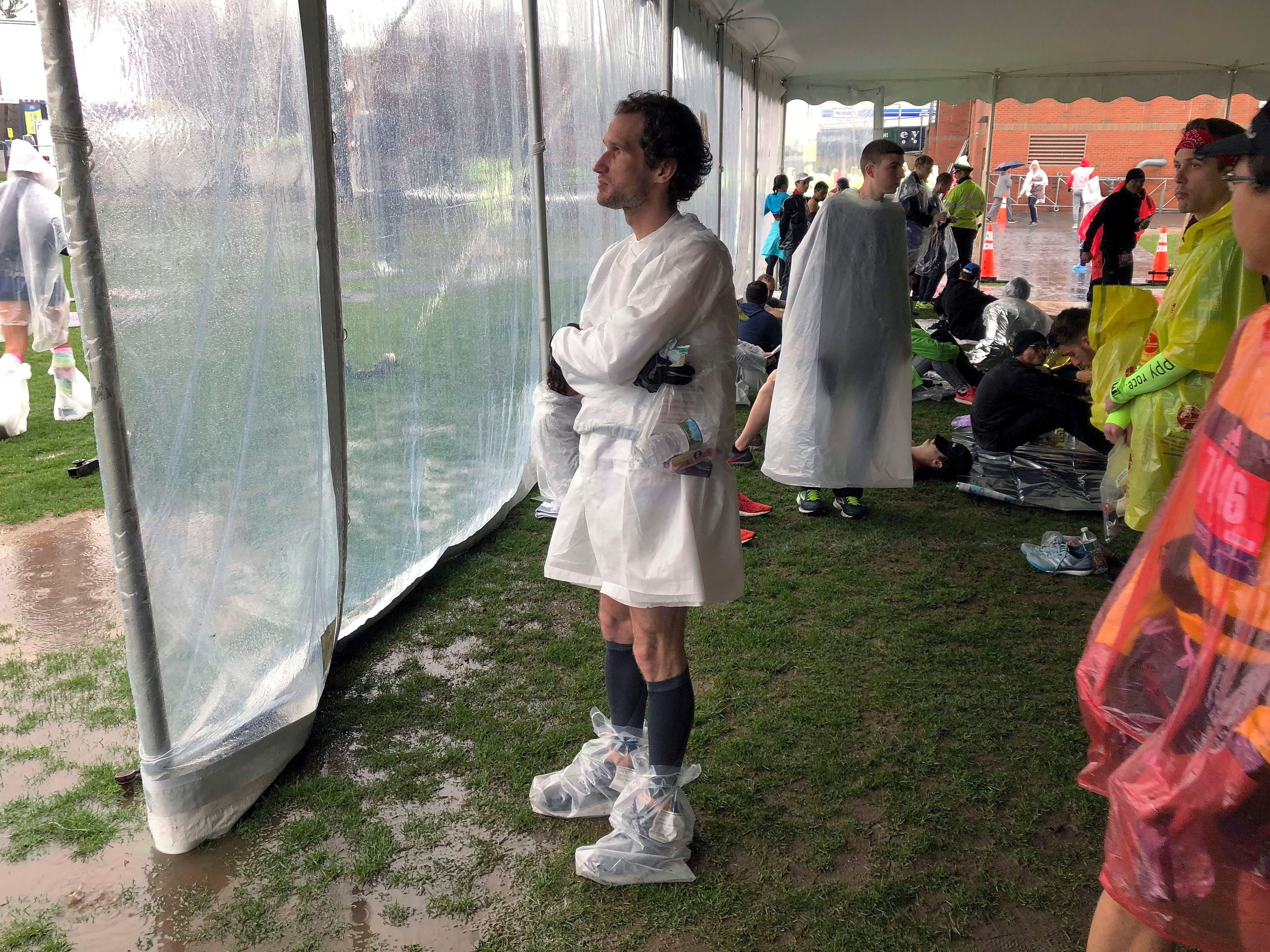 Lukas Chmatal, 35, originally from the Czech Republic and now a scientist at Massachusetts Institute of Technology, waits under a tent while it rains before the start of the 123rd Boston Marathon.