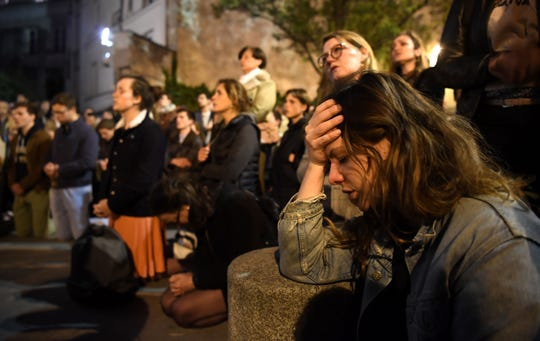 People kneel on the pavement as they pray outside while watching flames engulf Notre Dame Cathedral in Paris on April 15, 2019.