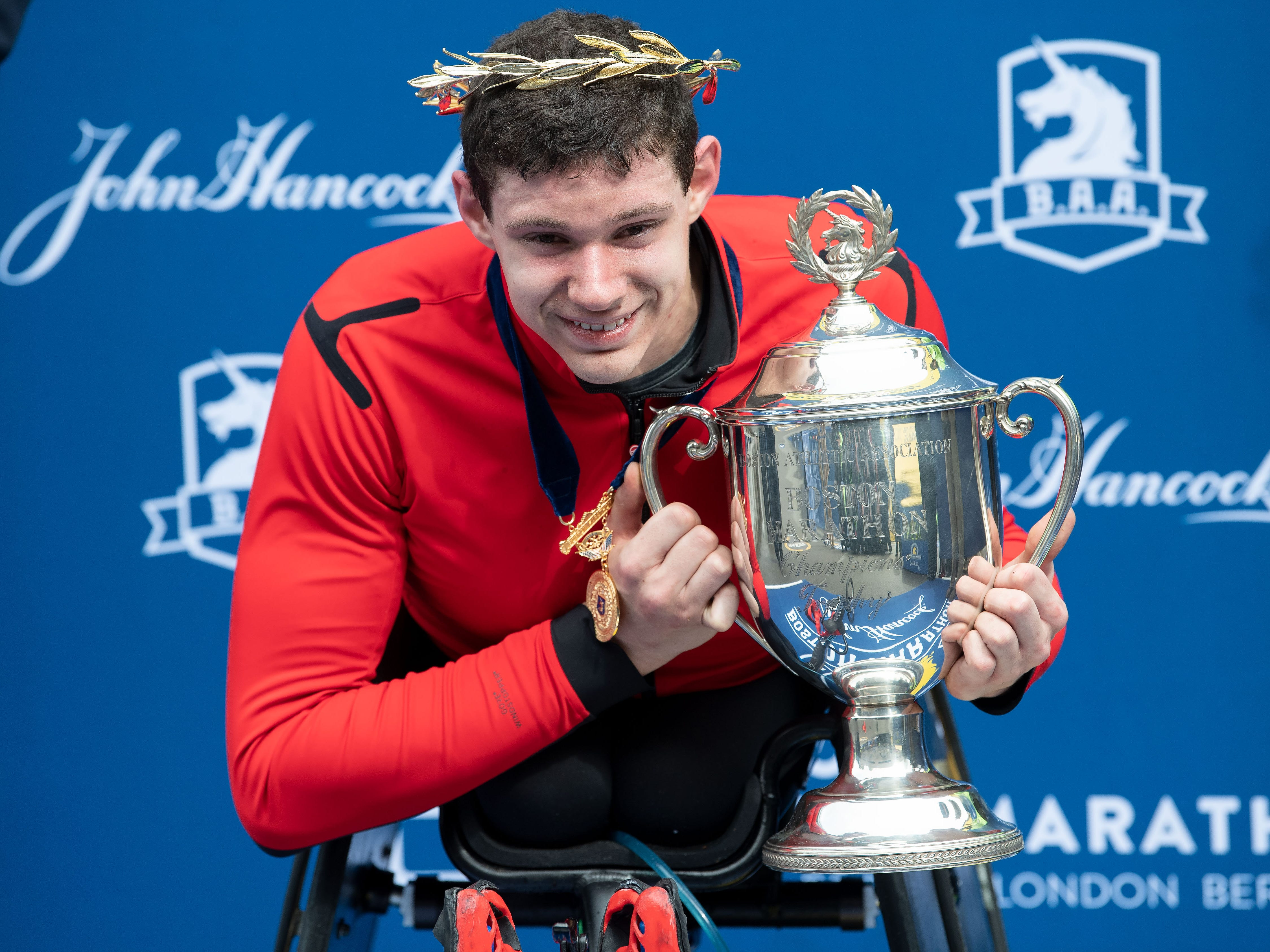 Daniel Romanchuk of the USA holds the trophy after winning the men's wheelchair division in the 2019 Boston Marathon.