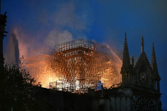 Flames are seen through scaffolding at Notre Dame in Paris during a fire on April 15, 2019.