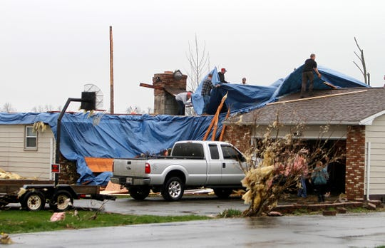 People work to cover the holes in a roof after severe weather damaged homes on Plymouth Springmill Road just south of the intersection of Ohio Route 96 in Shelby, Ohio, on April 14, 2019.