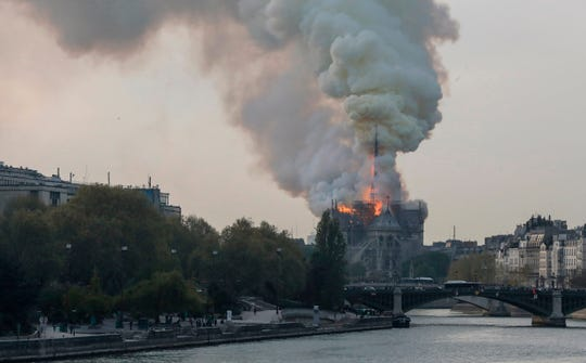 Smokes ascends as flames rise during a fire at the landmark Notre Dame Cathedral in central Paris on April 15, 2019.