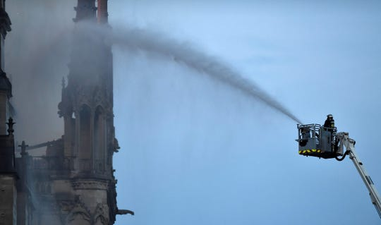 A fire fighter douses flames during a fire at the Notre-Dame de Paris Cathedral on April 15, 2019.