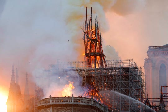 Smoke and flames rise during a fire at the landmark Notre Dame Cathedral in central Paris on April 15, 2019.