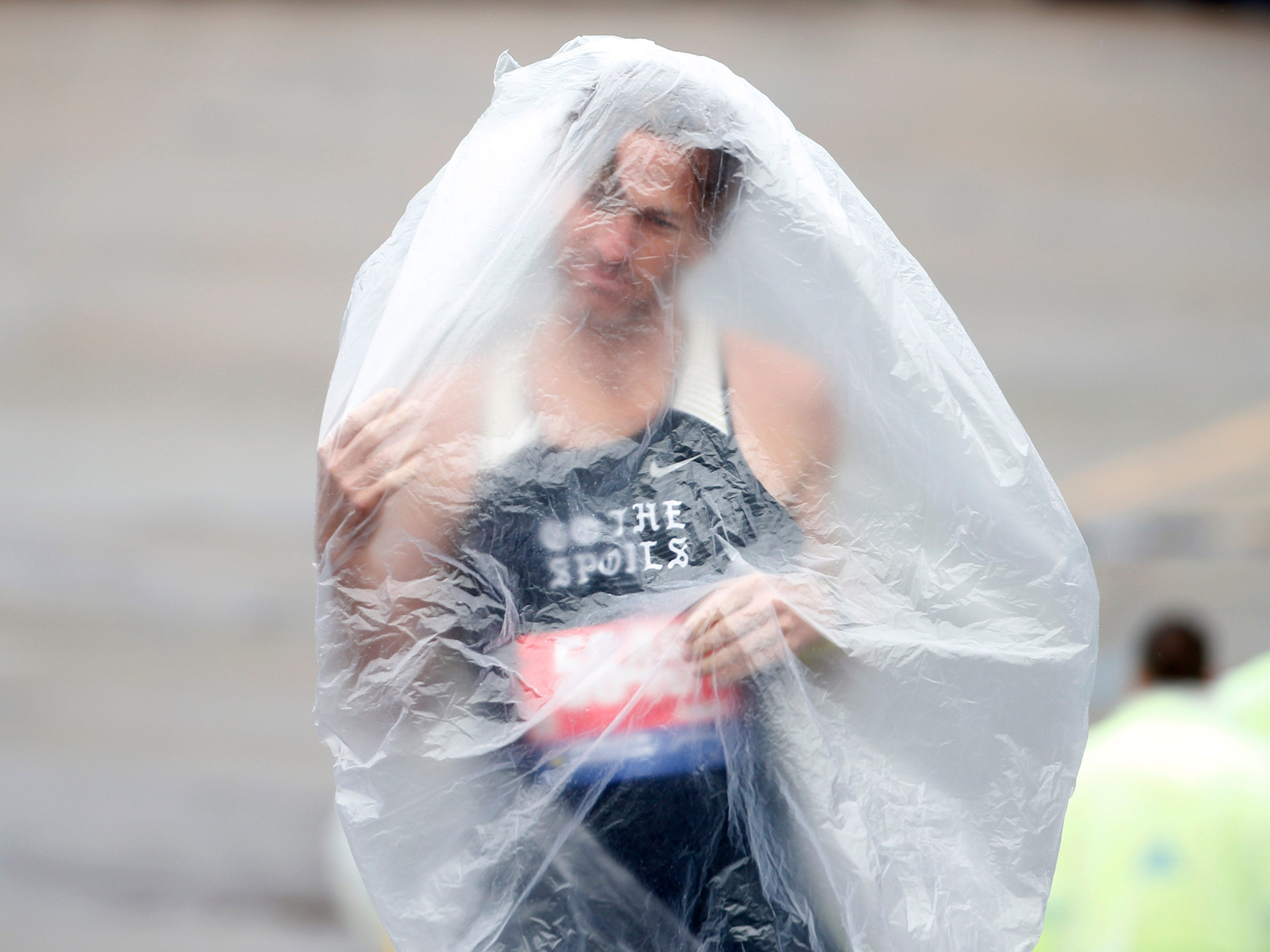 Runner Kyle Rodemacher struggles with his poncho prior to the 2019 Boston Marathon.