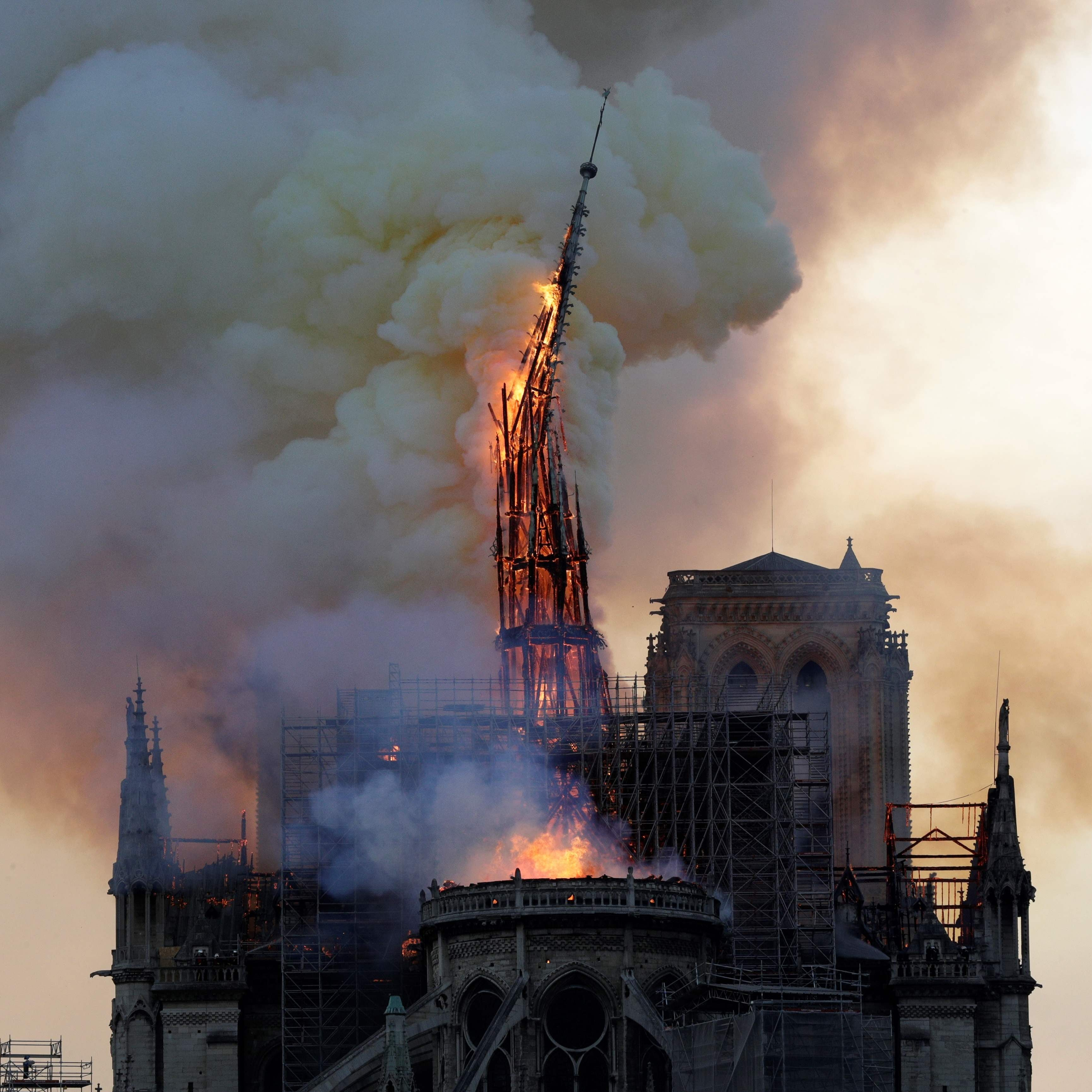 The steeple of the landmark Notre-Dame Cathedral collapses as the cathedral is engulfed in flames in central Paris on April 15, 2019.