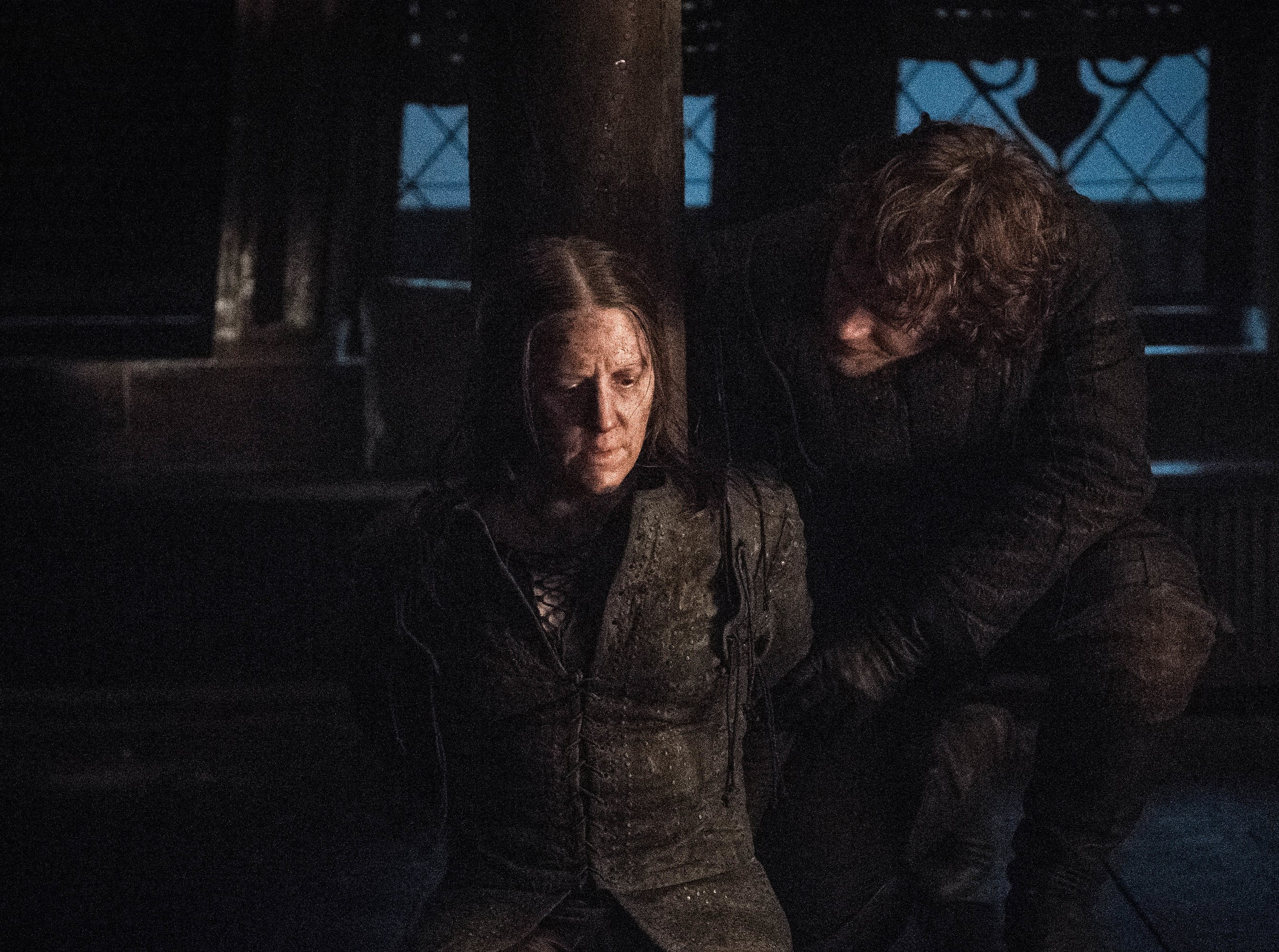 Theon Greyjoy (Alfie Allen) talks with a tied-up Yara Greyjoy (Gemma Whelan).