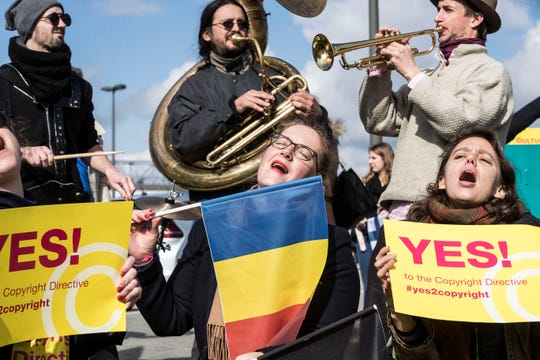 In this Tuesday March 26, 2019 file photo, people gather at the front of the European Parliament building in Strasbourg, France, to show their support for the copyright bill. The European Union approved on Monday April 15, 2019, a copyright law that aims to give more protection to artists and news organizations but which critics say will stifle freedom of speech and online creativity and punish smaller web companies.