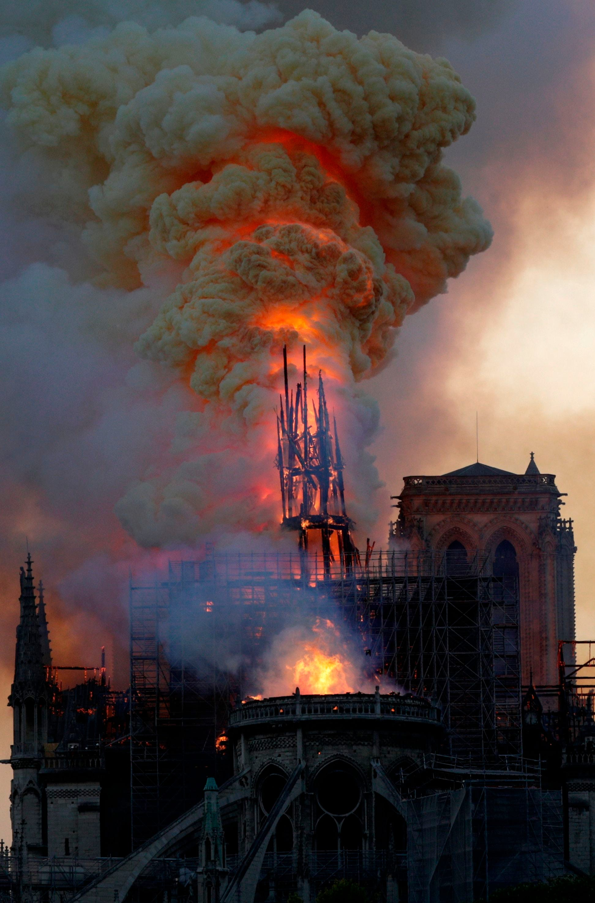 The steeple of Notre Dame collapses as the iconic cathedral burns on April 15, 2019, in Paris.