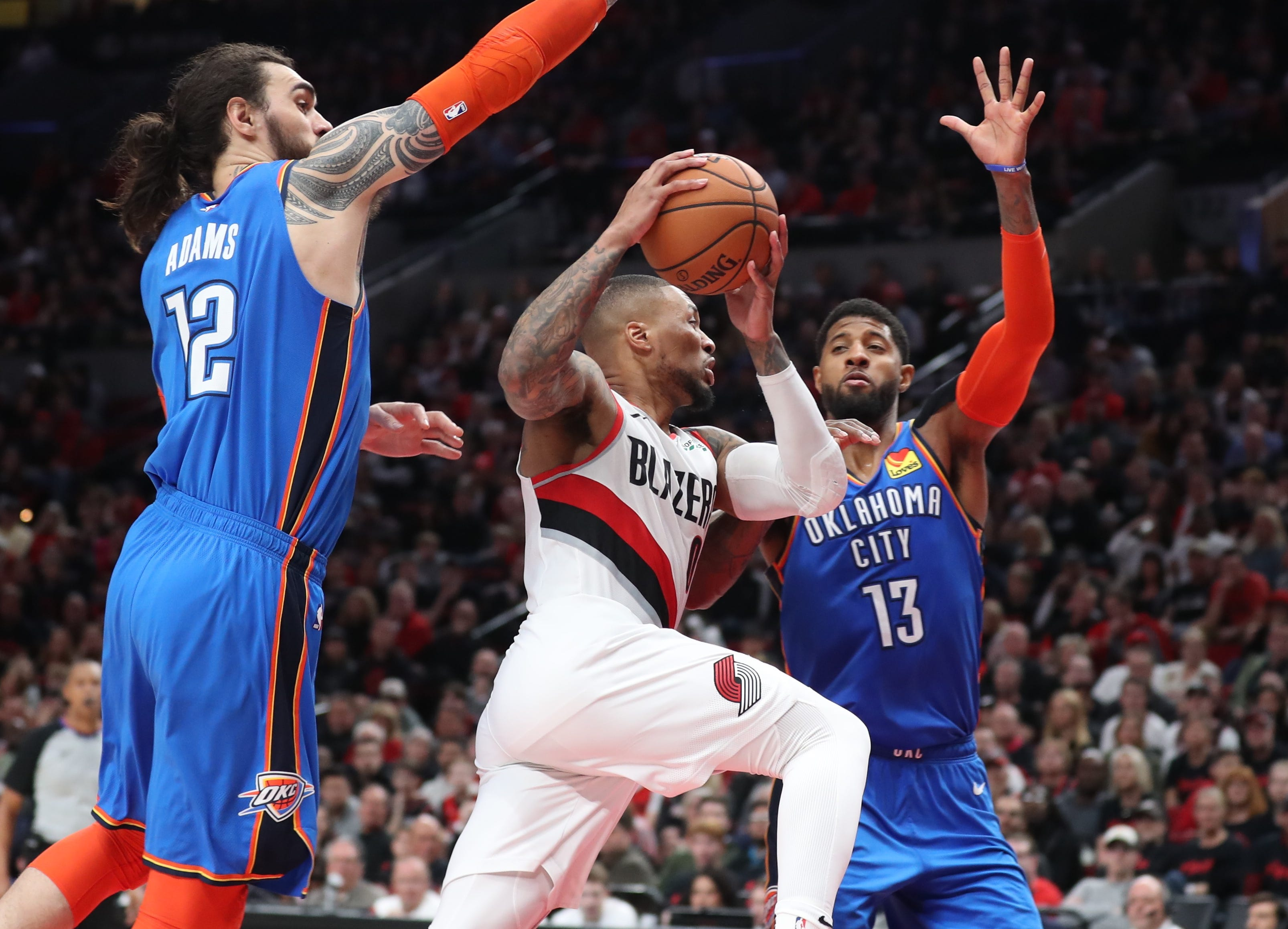 April 14: Trail Blazers guard Damian Lillard tries to drive between Thunder defenders Steven Adams and Paul George during Game 1.