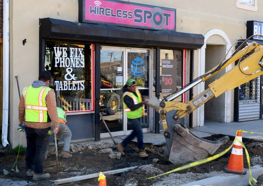 A crew repairs the sidewalk outside the Wireless Spot at 804 Main Street in Asbury Park Tuesday, April 16, 2019.  This business is owned by a Jackson man who is alledgely involved in a sprawling drug operation that involved money laundering through Bitcoin.