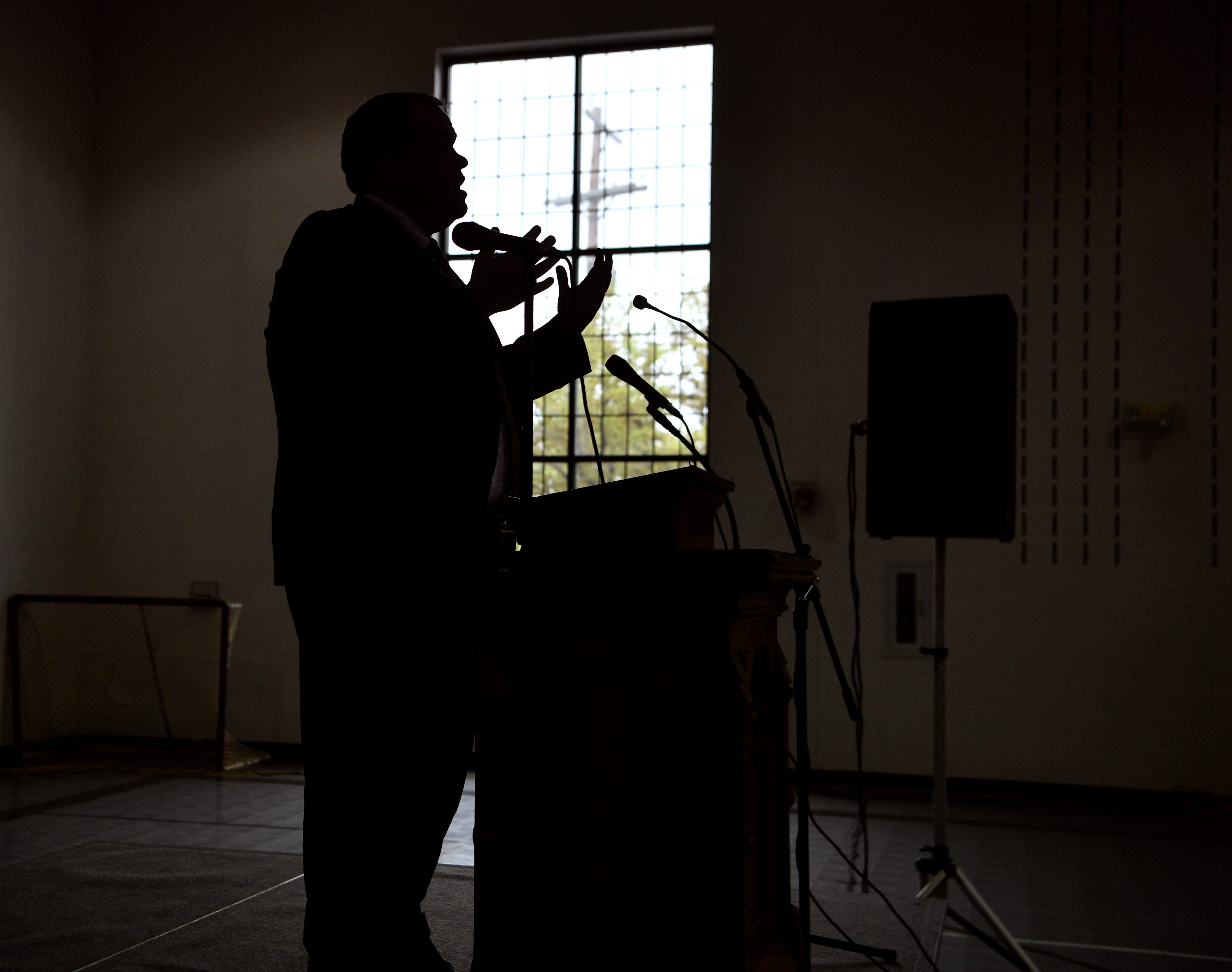 Framed by a window in the First Central Presbyterian Church gymnasium, Ben Siburt speaks to the audience during Tuesday's Holy Week service.