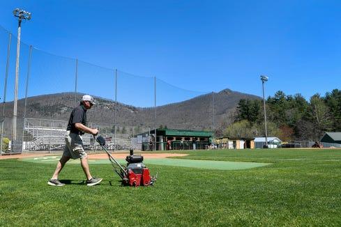 Scott Beam, an assistant coach for Reynolds High School baseball, tends to the grass at the school's baseball field April 10, 2019.