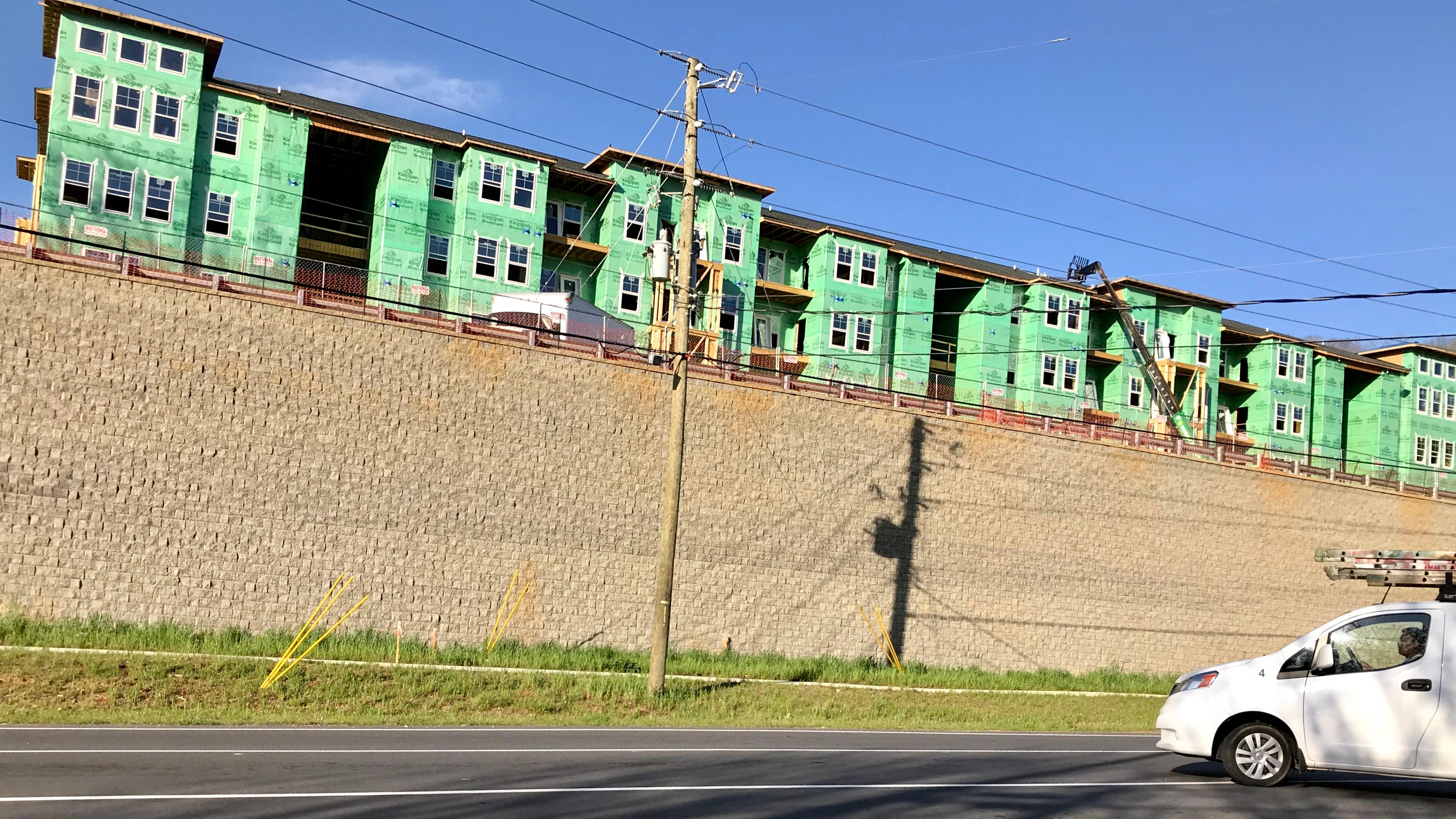 A berm and greenery will be installed along the large wall fronting the Hawthorne at Mills Gap apartments, but not until construction is wrapping up.