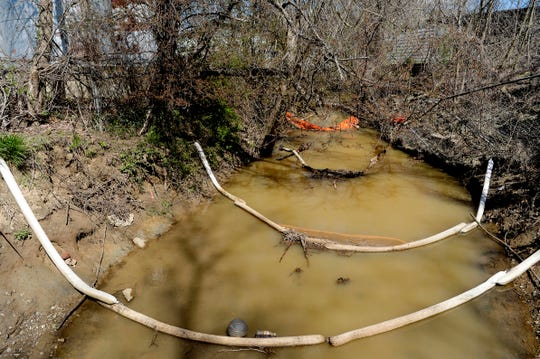 Oil absorbing booms float on the surface of Sweeten Creek April 9, 2019. A leak from an Asheville Oil fuel tanks has been seeping into the French Broad River tributary since November.