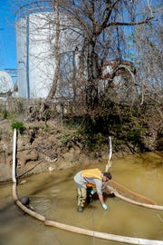 Brett Laverty, a hydrogeologist with the N.C. Department of Environmental Quality's Water Resources Division, takes a water sample from Sweeten Creek April 9, 2019, as Asheville Oil tanks tower in the background. A leak from one of the fuel tanks has been seeping into the French Broad River tributary since November.